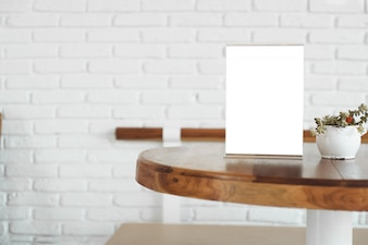 Menu Card Holder with white sheet of paper on table in cafe.