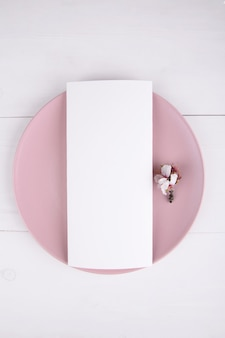 Menu card with blooming almond branch on a pink plate, design element for wedding.