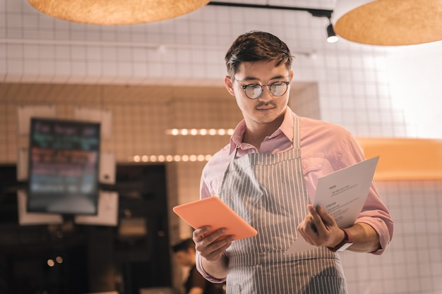 Меню ресторана. красивый мужчина-предприниматель в полосатом фартуке держит меню своего ресторана