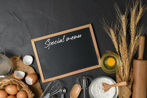 Menu text on blackboard and fresh eggs, cake flour  with kitchen utensils for pastries