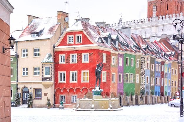 폴란드 포즈난의 눈 덮인 겨울날 구시가지의 올드 마켓 스퀘어에 있는 상인들의 집과 분수