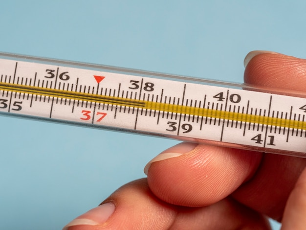 Mercury thermometer in the hand of a woman isolated on a blue background. temperature measurement using a thermometer. high fever and illness. close up