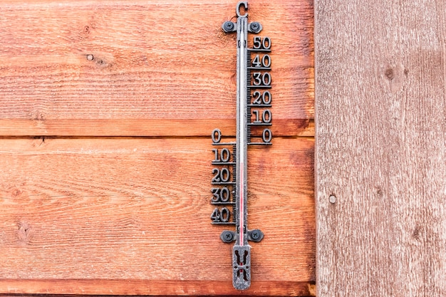 Mercury thermometer on wooden wall outside at -10 degrees celsius