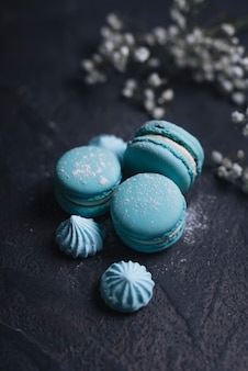 Merengue with stacked of blue macaroon on textured background