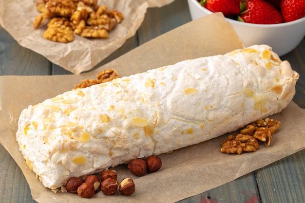 木製のテーブルの羊皮紙にナッツとメレンゲのケーキ