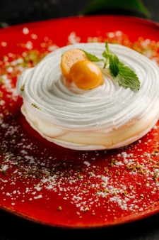 Meringue cake with whipping cream and citrus fruit on the top in a red plate.