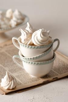 오래 된 잡지에 흰색 및 녹차 컵에 머랭 쿠키