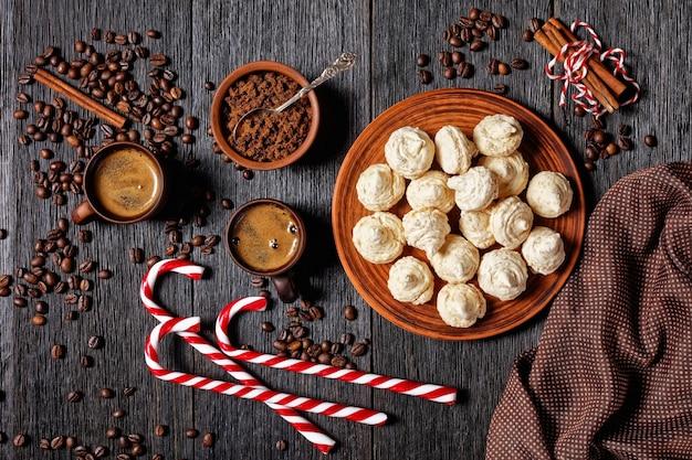 머랭 쿠키는 어두운 나무 배경에 크리스마스 사탕수수, 커피 컵, 커피 콩, 갈색 설탕, 계피 스틱이 있는 접시에 제공됩니다.