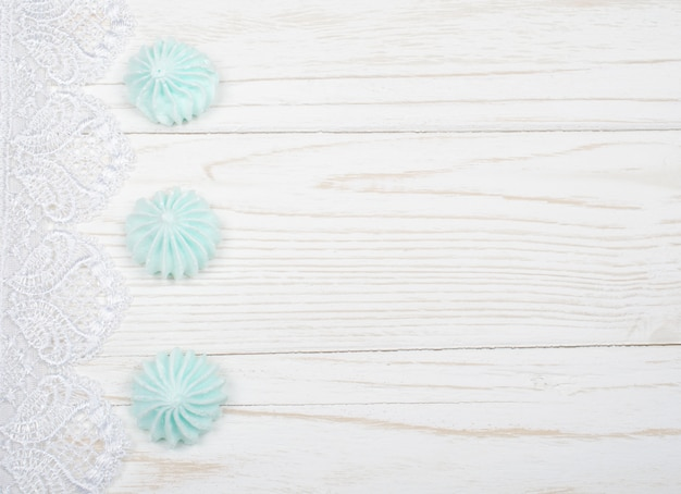 Meringue cookies and white lace on a white wooden background