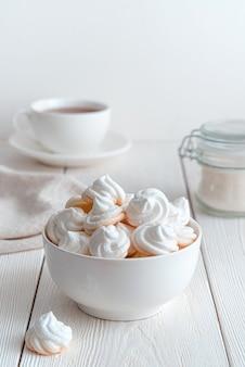 Десерт безе на фоне чашки чая, сахара и салфеток. вертикальный вид. концепция десертов.