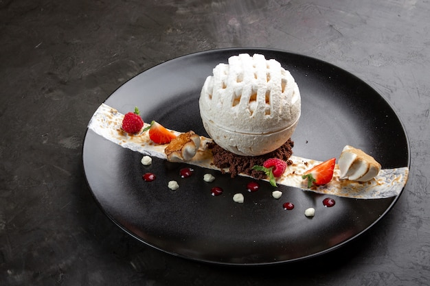 Meringue dessert with raspberries and strawberries in a black plate on a black background