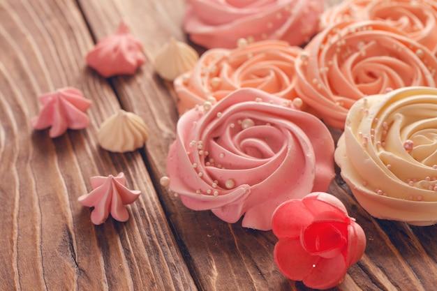 バラや花の形をした淡いピンクのメレンゲ。メレンゲはたくさんのケーキの飾り、クローズアップです。