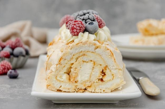 メレンゲロールパブロバケーキとクリームとラズベリーのブラックベリーとブルーベリー