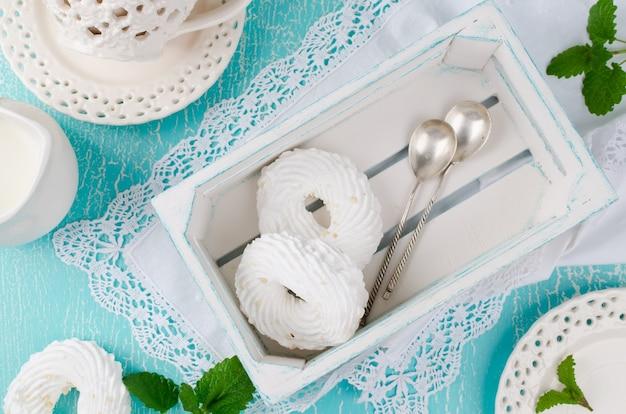 ターコイズブルーの背景に白い木製の箱のメレンゲ。素朴なスタイル