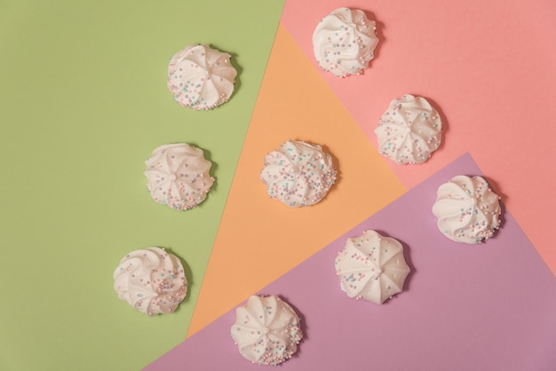 Meringues on light pastel background.