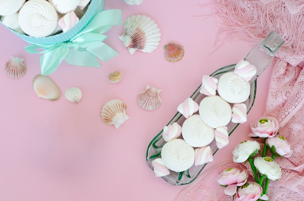 Meringues and marshmallows on handcrafted transparent serving plate on pastel pink background.