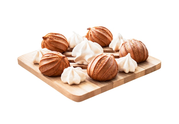 Meringues and mini eclairs or baked cakes on wooden board. dessert food isolated on white background