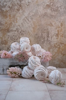 Meringues in a wooden box and pink flowers