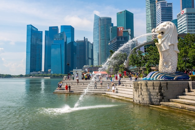 The merlion fountain in the background of skyscrapers and tourists