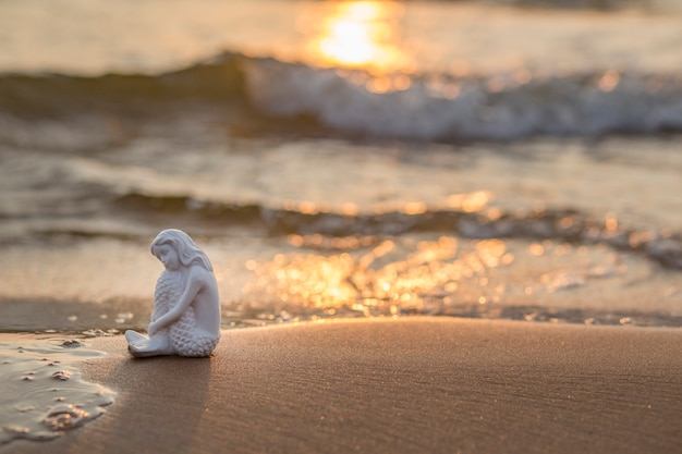Mermaid figure sits on the sand by the sea