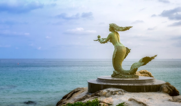 Mermaid statue and children at sai kaew beach in samed island