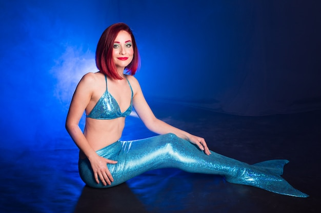 Mermaid with red hair resting on blue