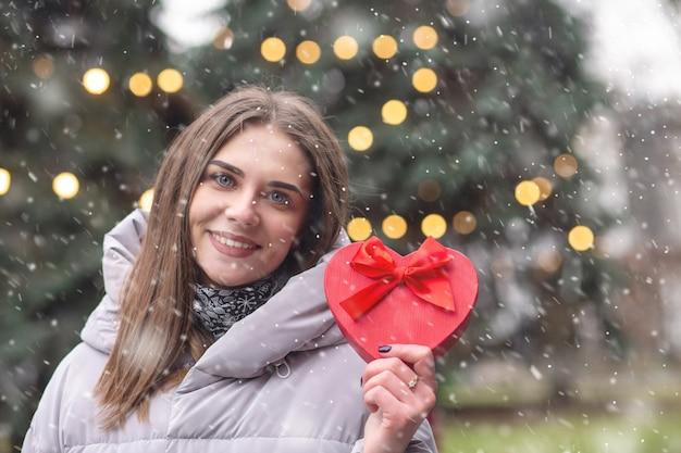 陽気な金髪の女性は、降雪時に新年の装飾が施された通りでガートボックスを保持している灰色のコートを着ています。空きスペース