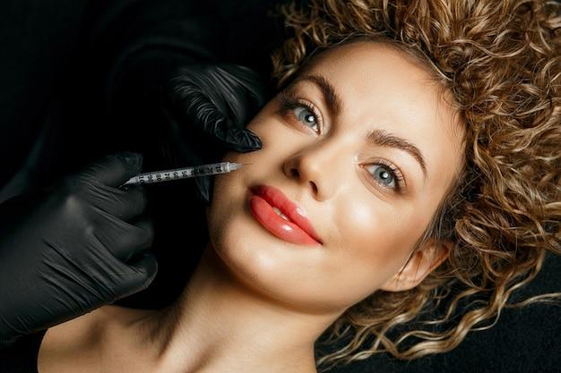 Веселая блондинка с инъекцией наполнителя в лицо. концепция косметологии. вид сверху