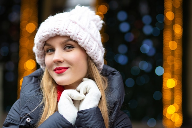 ボケと花輪の背景の上の通りでポーズをとってニット帽をかぶった赤い口紅と陽気なブロンドの女性