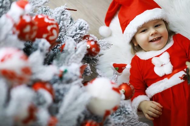 메리 밝은 크리스마스. 사랑스러운 아기는 크리스마스를 즐길 수 있습니다. 어린 시절의 추억. 산타 소녀 어린 아이는 집에서 크리스마스를 축하합니다. 가족 휴가. 소녀 귀여운 아이 쾌활한 분위기는 크리스마스 트리 근처에서 재생합니다.