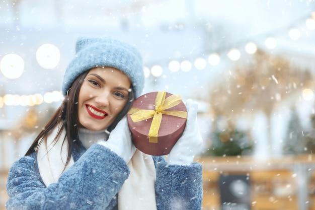 降雪時のクリスマスフェアでギフトボックスを保持している冬のコートの陽気なブルネットの女性。テキスト用のスペース