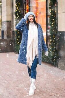 陽気なブルネットの女性は、降雪時に街を歩いているニットのライトピンクのキャップとスカーフを身に着けています。テキスト用のスペース
