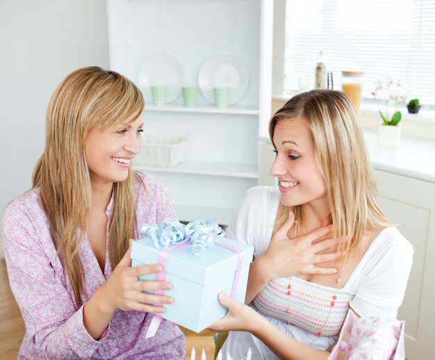 Merry caucasian woman giving a present to her surprised friend for her birthday in the kitchen