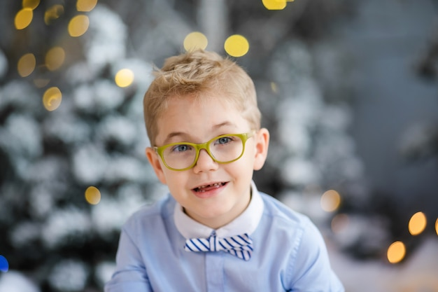Merry ccharming little boy is sitting at home, snowy winter decorated tree