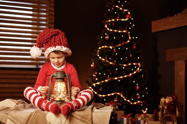 메리 크리스마스와 즐거운 휴일 어린 소년 크리스마스 트리 새 해, 엘 프에 랜 턴과 함께 앉아있다.