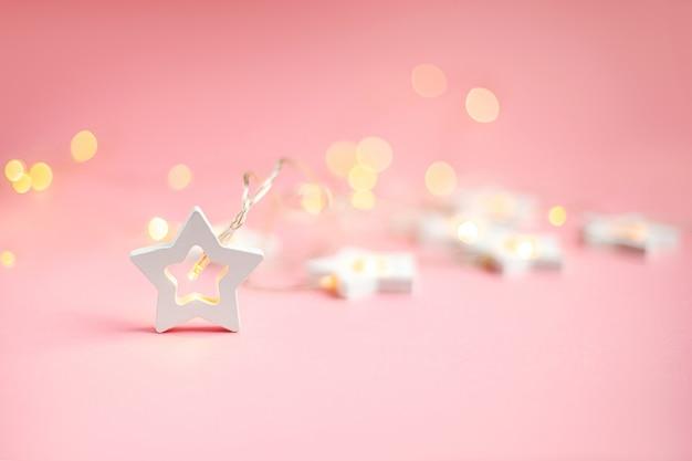 メリークリスマスと幸せな休日のバナーとグリーティングカード。 。コピースペースと黄色のクリスマスライトボケの木製の星。冬の休日のテーマ。壁紙。