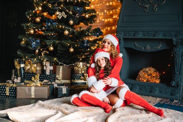 즐거운 성탄절과 즐거운 휴일 보내세요! 크리스마스 의상을 입은 어린 딸을 둔 아름다운 어머니는 크리스마스 트리 근처에서 함께 시간을 보냅니다.