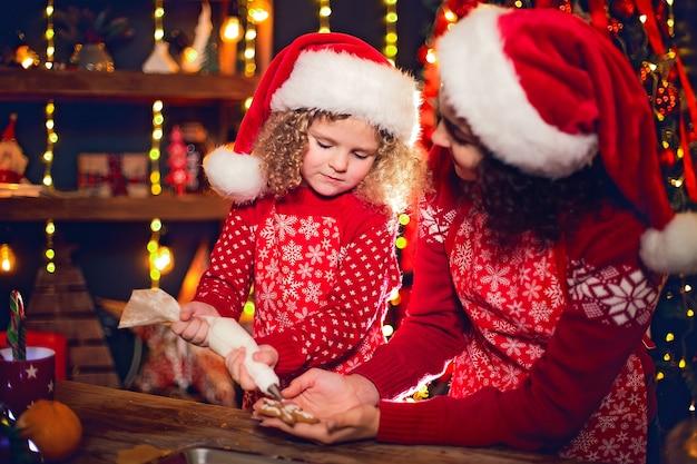 Счастливого рождества и счастливых праздников. жизнерадостная милая курчавая маленькая девочка и ее старшая сестра в шляпах santas варя печенье рождества.
