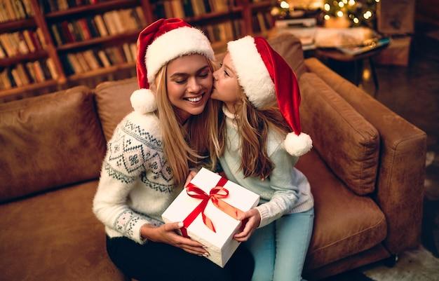 즐거운 성탄절과 즐거운 휴일 보내세요! 쾌활한 엄마와 그녀의 귀여운 딸 소녀가 선물을 교환합니다. 부모와 어린 아이가 실내 나무 근처에서 즐거운 시간을 보내고 있습니다. 방에 선물을 들고 사랑하는 가족.
