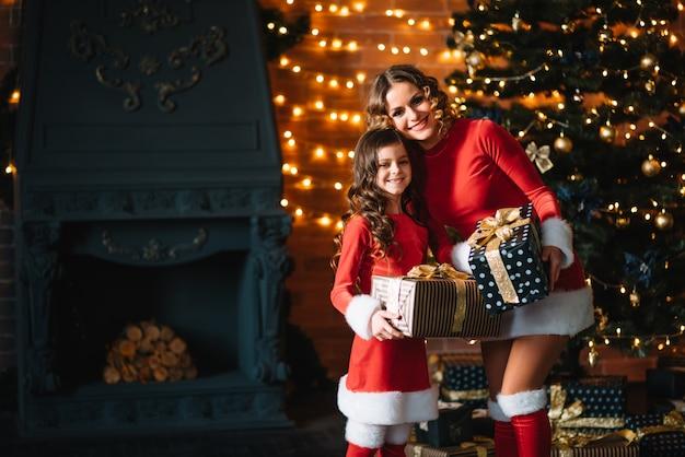 メリークリスマスとハッピーホリデー!陽気なお母さんとクリスマスの衣装を着たかわいい娘の女の子がプレゼントを交換します。