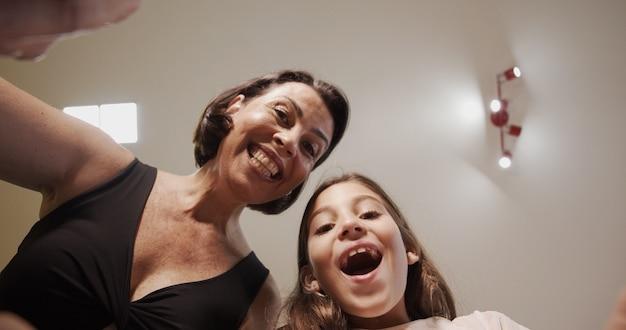 С рождеством и праздником! веселая мама и ее милая дочь девочка открывают рождественский подарок. родитель и маленький ребенок веселятся в помещении. вид изнутри коробки.