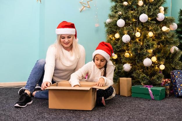 즐거운 성탄절과 즐거운 휴일 보내세요. 쾌활 한 엄마와 그녀의 귀여운 딸 소녀 크리스마스 선물을 여는. 부모와 어린 아이가 실내 크리스마스 트리 근처에서 즐거운 시간을 보내고 있습니다. 상자 내부에서 본 모습입니다.