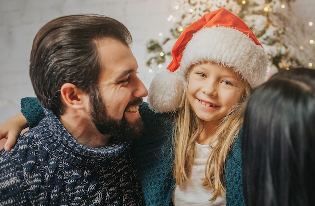 메리 크리스마스와 해피 홀리데이 쾌활한 어머니, 아버지와 선물을 교환하는 그녀의 귀여운 딸 소녀. 부모와 어린 아이 실내 크리스마스 트리 근처 재미. 아침 크리스마스.