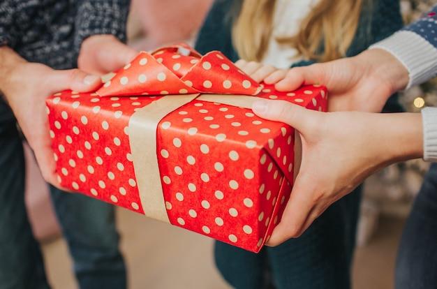 Веселого рождества и счастливых праздников веселая мать, отец и ее милая дочь девочка обмениваются подарками.