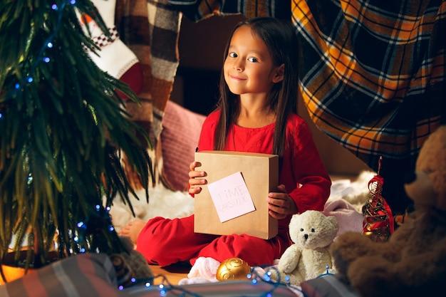 С рождеством и праздником. милая маленькая девочка ребенка пишет письмо деду морозу возле елки дома в помещении. праздник, детство, зима, концепция празднования