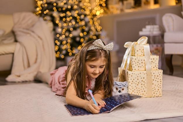 メリークリスマスとハッピーホリデー。かわいい小さな子供の女の子は、屋内のクリスマスツリーの近くのサンタクロースに手紙を書きます。