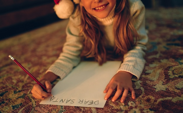 メリークリスマスとハッピーホリデー!かわいい小さな子供の女の子は、屋内のクリスマスツリーの近くのサンタクロースに手紙を書きます。