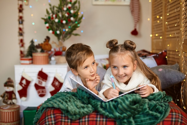 メリークリスマスとハッピーホリデー。屋内のクリスマスツリーの近くでサンタクロースに手紙を書いているかわいい子供たち。