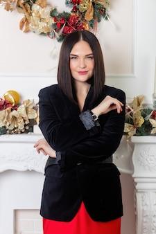 즐거운 성탄절과 즐거운 휴일 보내세요! 크리스마스 트리 조명 배경 위에 빨간 치마와 검은 재킷에 우아한 아가씨. 새해 복 많이 받으세요.
