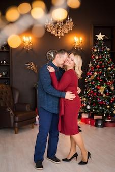 메리 크리스마스, 해피 홀리데이. 가족, 한 남자와 한 여자가 크리스마스 트리의 배경에 대해 포용합니다. 새해 복 많이 받으세요